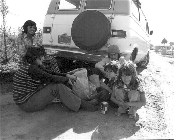A migrant worker family eating in the shade of their van